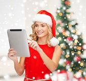holidays, technology and people concept - smiling woman in santa helper hat with tablet pc computer over living room and christmas tree background