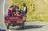 PUNO, PERU, MAY 6, 2014: Peruvian countryside in region of Lake Titicaca - Local people travel on motorcycle trailer