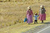 PUNO, PERU, MAY 6, 2014: Peruvian countryside in region of Lake Titicaca - Local women with a little boy walk at roadside