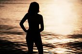 Women at sea sunset. Silhouette of the bikini women backlit by g