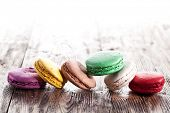 Colourful french macaron on an old wooden table.