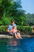Family of father and his little daughter sitting at edge of swimming pool