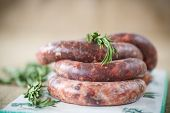 foto of raw chicken sausage  - home hepatic raw sausage with rosemary on a table - JPG