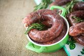 stock photo of raw chicken sausage  - home hepatic raw sausage with rosemary on a table - JPG