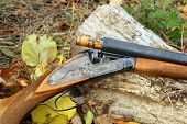 foto of shotgun  - A wooden retro shotgun with shot in autumn style - JPG