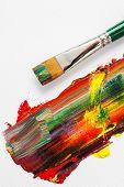 Paintbrush And Mixed Rainbow Oil Paints On Artist Canvas