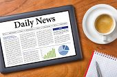 Tablet on a wooden desk - Daily News