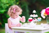 stock photo of baby doll  - Adorable funny toddler girl with curly hair wearing a colorful dress on her birthday playing tea party with a teddy bear doll toy dishes cup cakes and muffins in a sunny summer garden - JPG