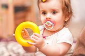 pic of nipple rings  - little girl sitting playing with a toy ring - JPG