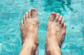 Bare feet of a young Asian woman dangling over sparkling blue water in a tiled swimming pool with dancing sunlight in a wellness, spa and summer vacation concept