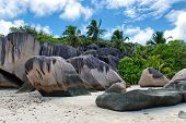 Close up Big Historic Rocks and Tall Green Trees on the Landscape of Seychelles Island with White Beach Sand.