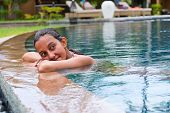 Attractive young Asian woman with wet hair relaxing in a swimming pool leaning on the tiled surround daydreaming and staring off into space
