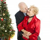 Senior couple dressed for the holidays.  He's giving her a kiss on the cheek.  Isolated with Christmas tree in background.