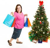 Pretty plus sized woman excited about bargain shopping for Christmas.  Full body isolatedo on white.