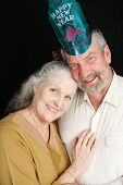 Beautiful couple in their sixties posing for a romantic portrait on New Year's Eve.  Black background.