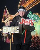 A senior man happily planting Christmas yard signs in front of his decorated house at night.