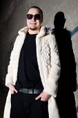 picture of pimp  - Man in long white chinchilla fur coat posing like a pimp near the grungy 