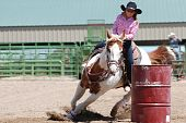 foto of barrel racing  - Young cowgirl riding a beautiful paint horse in a rodeo competition - JPG