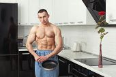 foto of pinafore  - Bodybuilder man in an apron standing in the kitchen holding a frying pan - JPG