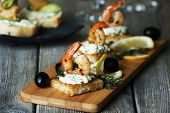 stock photo of canapes  - Appetizer canape with shrimp and olives on cutting board on table close up - JPG