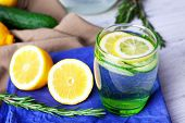 foto of cucumbers  - Fresh water with lemon and cucumber in glassware on napkin on wooden table - JPG
