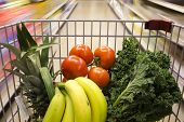 stock photo of grocery cart  - A shopping cart with veggies in motion in a grocery store - JPG