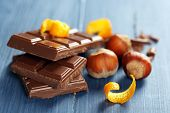 picture of orange peel  - Pieces of chocolate with orange peels on color wooden background - JPG