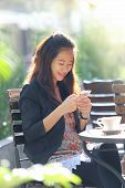 stock photo of handphone  - A portrait of a Young businesswoman work oudoor in a cafe - JPG