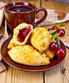 stock photo of patty-cake  - Sand patty with cherries on a brown plate - JPG