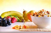 stock photo of fruit bowl  - Bowl of cereal with fruit on a white wooden table and fresh fruits behind overview - JPG