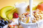 foto of cereal bowl  - Stream of milk falling into a bowl of cereal and fruits on a table with fruits and glass of milk background - JPG