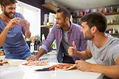 image of three life  - Three Male Friends Making Pizza In Kitchen Together - JPG
