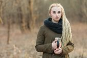 foto of dread head  - Young beautiful blonde hipster woman in scarf and parka with dreadlocks hairstyle posing on a blurry forest background with a thermos cup - JPG