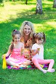 stock photo of eat grass  - Young beautiful woman with girls kids daughters sitting on grass smiling eating ice cream - JPG