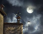 stock photo of wind vanes  - Antique roofs with weather vane rooster and chimneys in a beautiful night sky with full moon and clouds - JPG