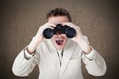 stock photo of binoculars  - Positive businessman using binoculars against weathered surface - JPG