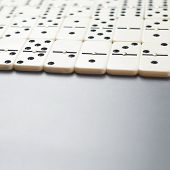 picture of over counter  - Multiple domino bones over the dark gray surface as a background composition with the shallow depth of field - JPG