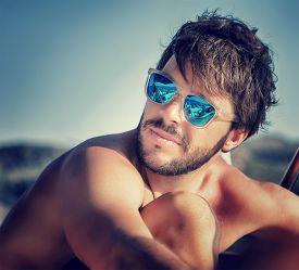 stock photo of macho man  - Closeup portrait of handsome man on the beach in mild sunset light - JPG