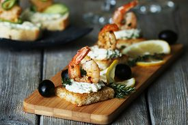 picture of shrimp  - Appetizer canape with shrimp and olives on cutting board on table close up - JPG