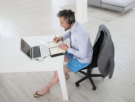 picture of stressless  - Businessman on video meeting from home in relaxed outfit - JPG