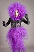 foto of transexual  - Drag queen in violet dress standing on gray background - JPG