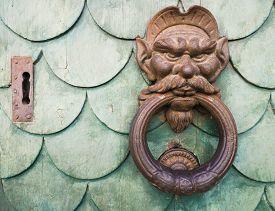 picture of goblin  - Iron goblin face doorknocker on green wooden door - JPG