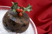 Christmas pudding with holly on glass dish dusted with icing sugar on a red cloth xmas