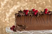 Festive Christmas roulade on glass cake stand decorated with chocolate dipped holly leaves and berries - gold bokeh background