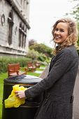 Side view of happy young woman putting plastic waste in garbage bin by street