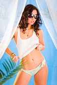 Glamour style photo of beautiful girl in sunglasses posing in summerhouse on beach.