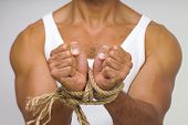Muscular man with hands tied by rope