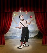 stock photo of circus clown  - Clown performing on stage with red curtains - JPG