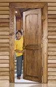 Boy opening a wooden door in front of his home