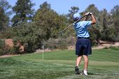 Young Male Hitting Ball On Green, Focus On Golfer